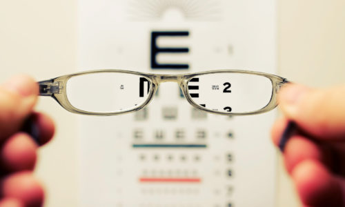 Person with blurry vision looking through glasses to see clearly.